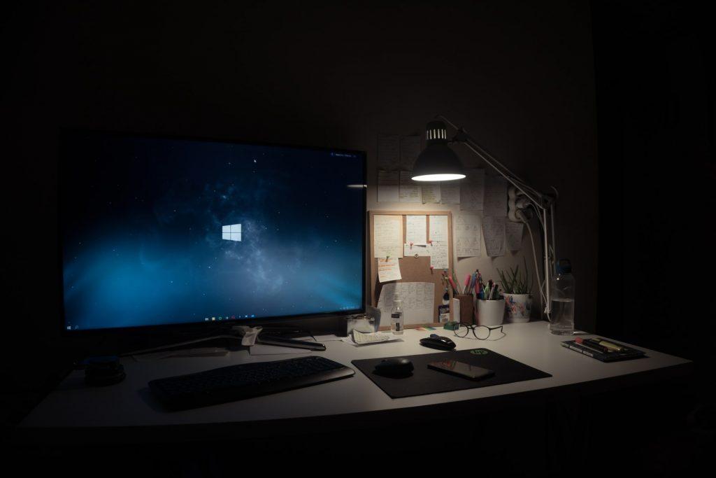 Monitor gaming en escritorio y un lampara de mesa