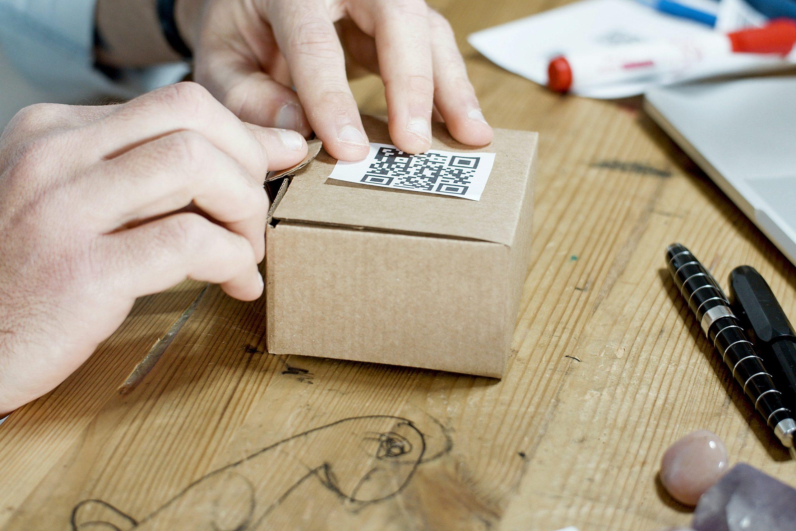Persona colocando codigo QR en paquete