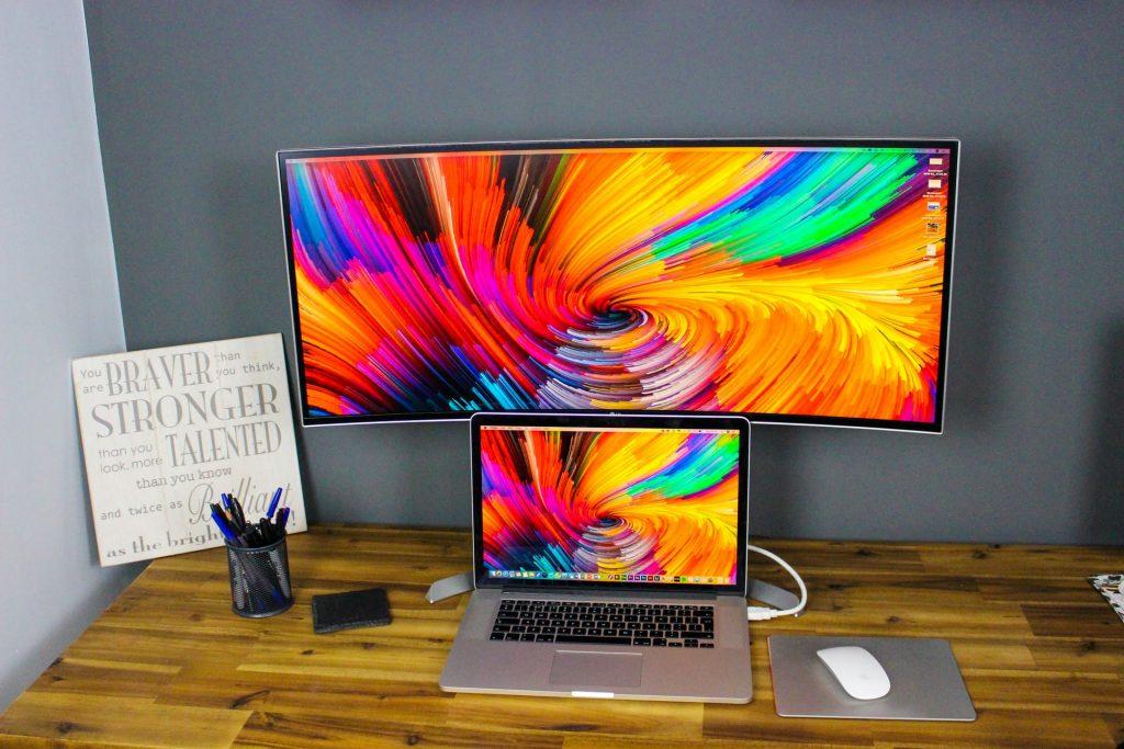 Monitor curvo atras de laptop sobre mesa