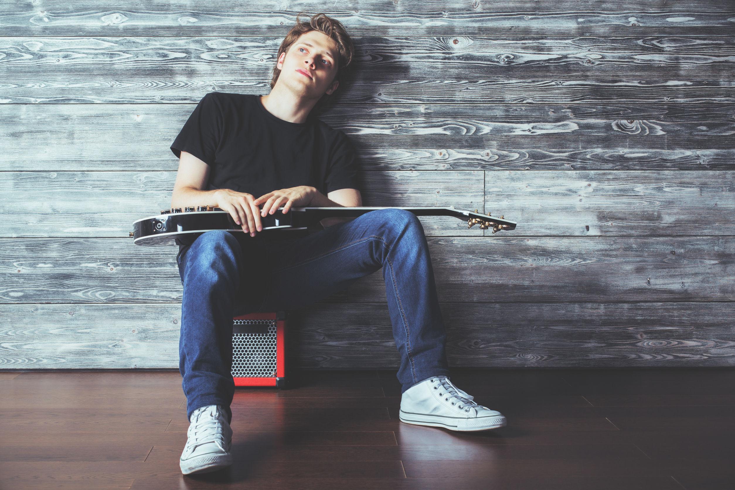Apuesto joven con la guitarra eléctrica que se sienta en el amplificador en el cuarto de madera