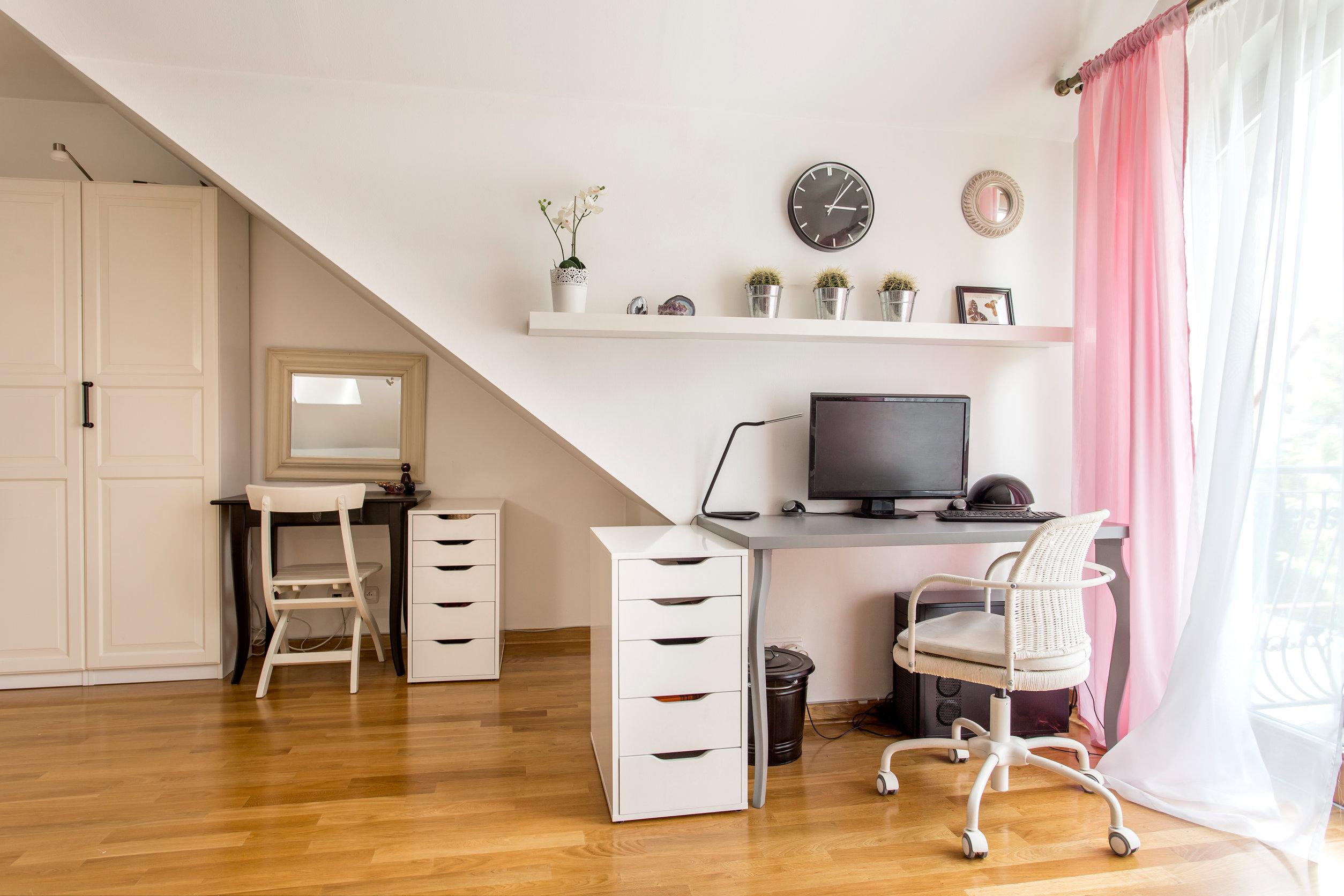 Sala de oficina en casa con escritorio, cómoda, armario, sillas, y ventana