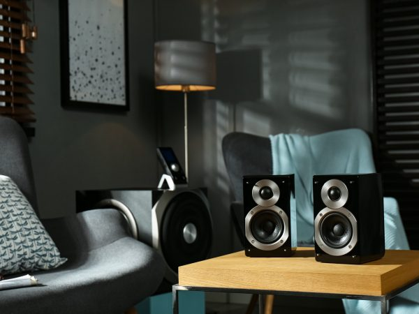 Modern audio speaker system on wooden table in living room