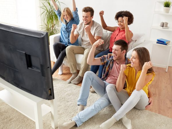 friendship, leisure, people and entertainment concept – happy friends with remote control and drinks watching tv at home