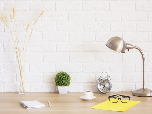 Creative desktop with glasses, alarm clock, notepad, coffee cup, wheat spikes and other items